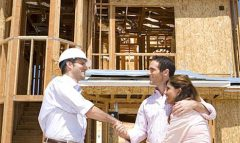 Young couple shaking hands with architect in front of partially built house, low angle view